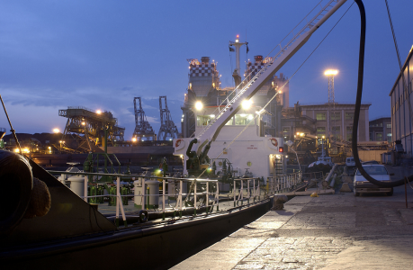A docked ship at twilight showing a hose linked from ship to shore